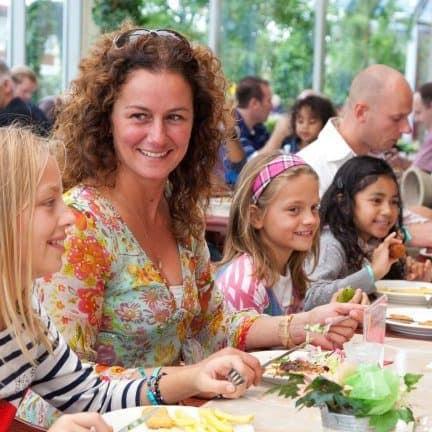 Familie aan het eten in het restaurant van Hotel en attractiepark Wunderland Kalkar in Kalkar, Duitsland