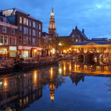 Gracht en verlichte brug in Leiden, Zuid-Holland