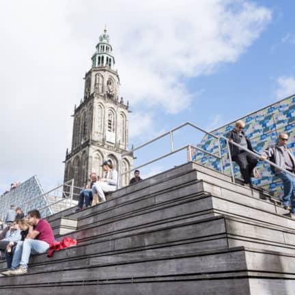 Mensen zitten op de trappen op de Grote Markt voor de Martinitoren in Groningen