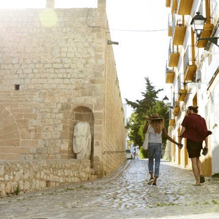 Stelletje loopt hand in hand door een oude straat op Ibiza