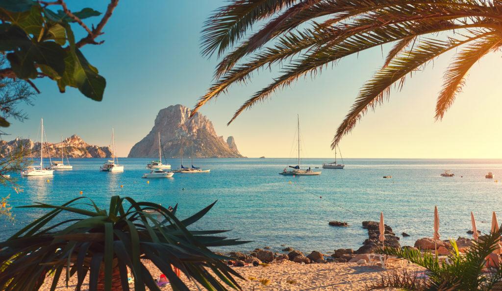 Strand van Cala d'Hort op Ibiza met zeilboten op zee en uitzicht op Es Vedra