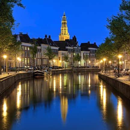 Uitzicht op een gracht met boten en de A-kerk in Groningen