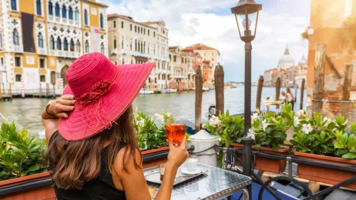 Vrouw geniet op een terras van een drankje met uitzicht op de Canale Grande in Venetië, Italië