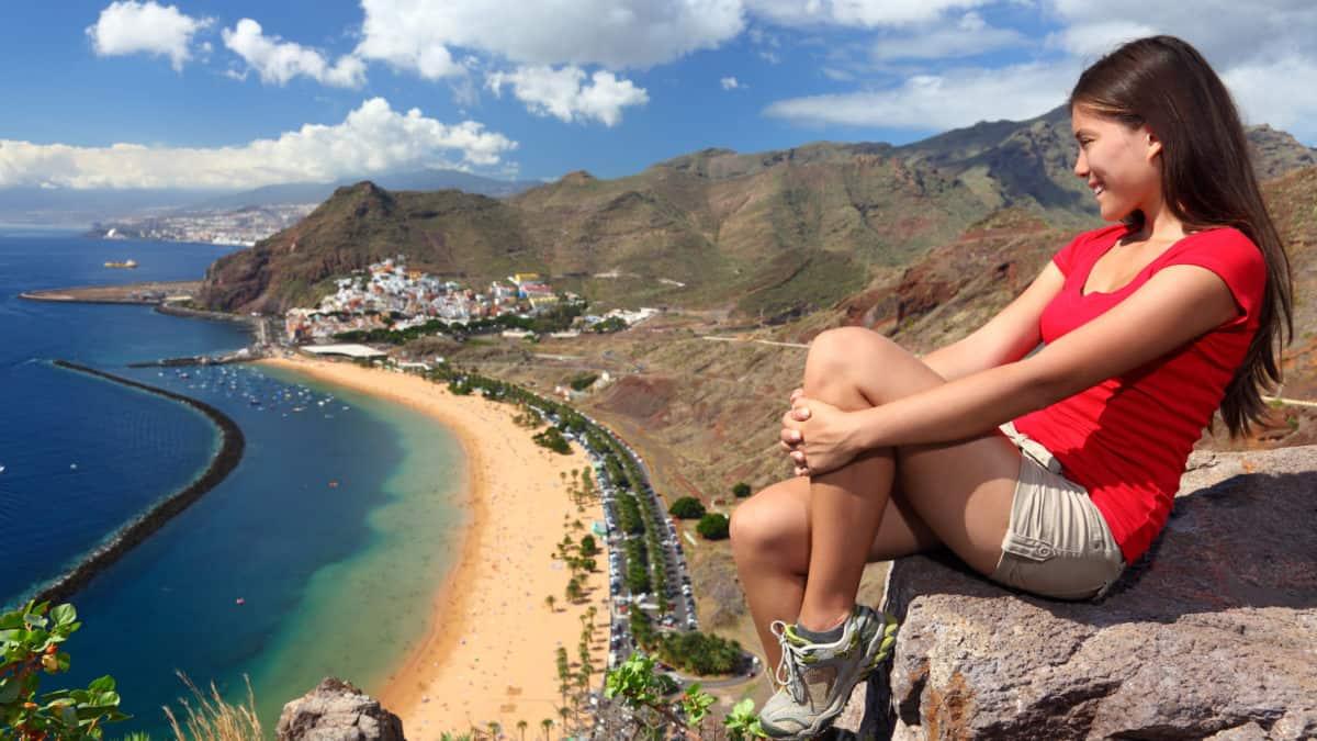 Vrouw kijkt op een rots uit over Playa De Las Teresitas op Tenerife
