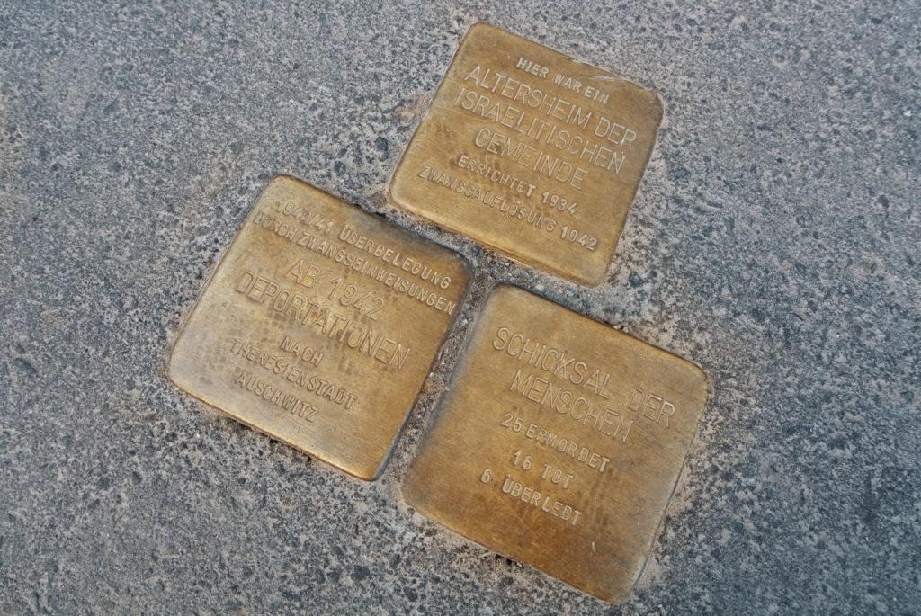 Drie struikelblokken (Stolpersteine) op een stoep in Berlijn, Duitsland