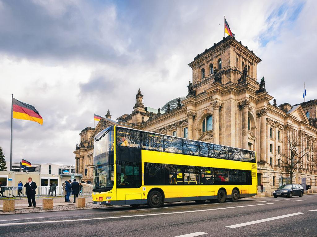 Gele toeristische bus bij het Reichstag gebouw in Berlijn, Duitsland