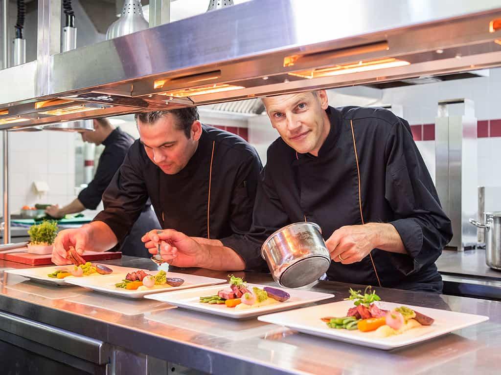 Koks bereiden maaltijd in restaurant van Fletcher Hotel-Restaurant De Klepperman