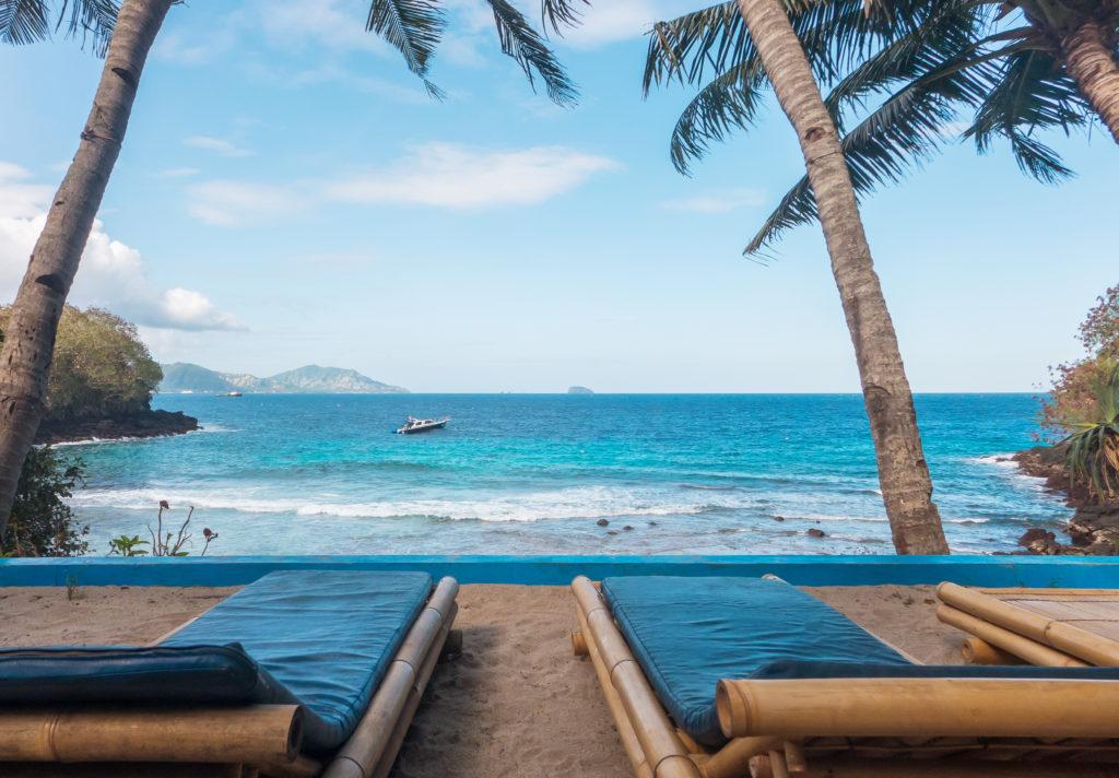 Ligbedden en palmbomen met uitzicht op zee bij het strand van Jimbaran op Bali, Thailand