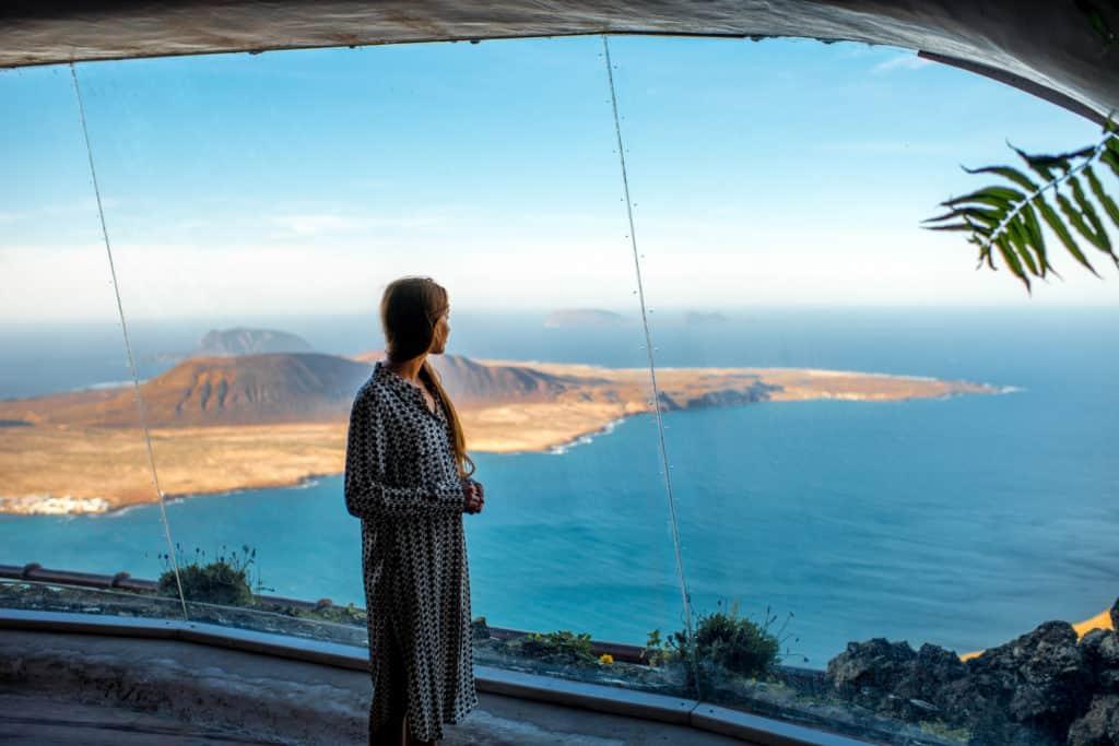 Toerist kijkt uit het raam naar Graciosa bij Mirador del Río op Lanzarote