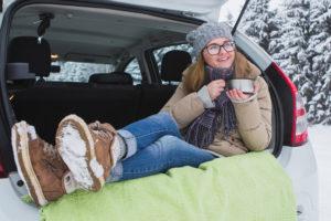 Jonge vrouw zit in de kofferbak van de auto en met een kop hete thee