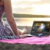 Vrouw kijkt televisie op haar laptop op een strand