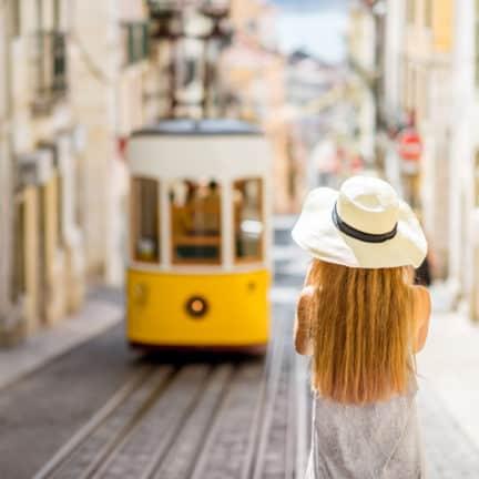 vrouw met hoed kijkt naar bekende gele tram lissabon portugal