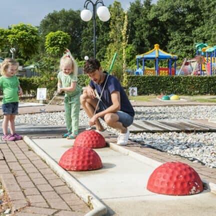 Vader met kinderen aan het midgetgolfen op Roompot Resort Arcen in Arcen, Limburg, Nederland