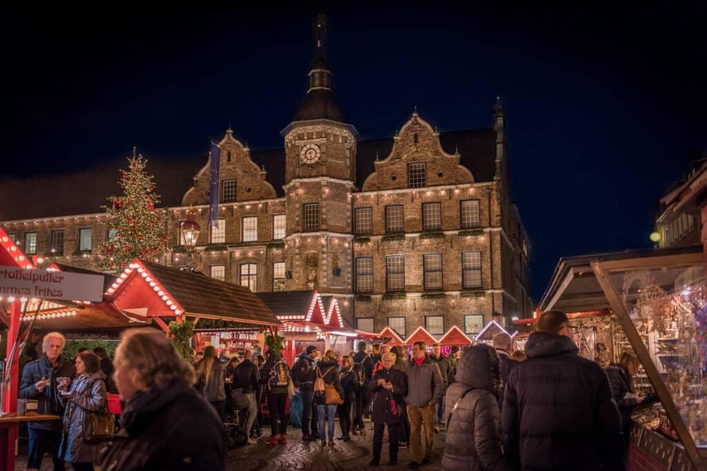 Verlichte kerstmarkt op beroemde Burgplatz met uitzicht op oude herenhuis in Düsseldorf, Duitsland