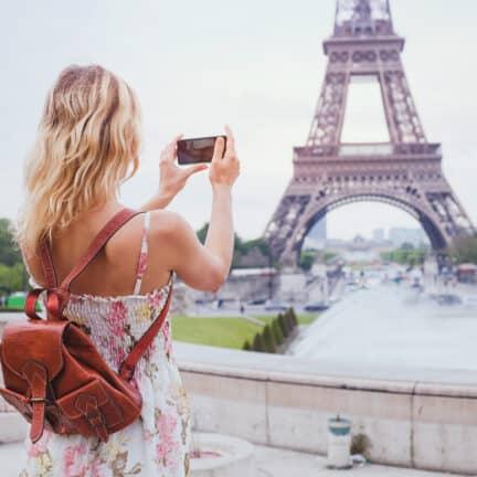 Vrouwelijke toerist met rugzak neemt een foto van de Eiffeltoren in Parijs, Frankrijk