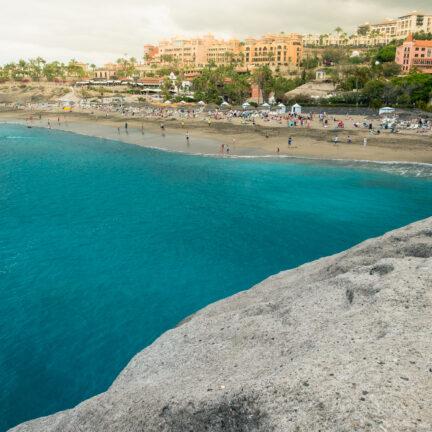 Uitzicht op de blauwe zee en het strand van El Duque in Costa Adeje, Tenerife