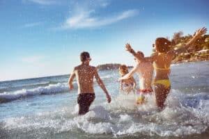 Vrienden springen in de zee tijdens zonsondergang