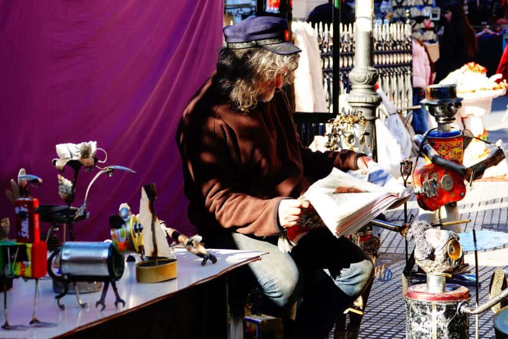 Man leest krant op de El Rastro markt in Madrid, Spanje
