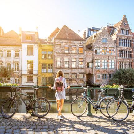 Vrouwelijke tourist kijkt naar huizen aan de gracht in Gent, België