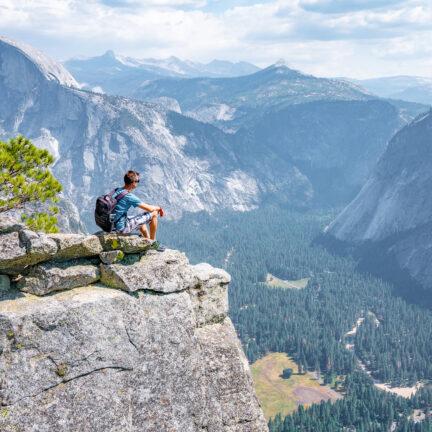 Man zit op de rand van de klif met uitzicht op El Capitan in Yosemite National Park