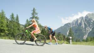 Wielrenner loopt met de fiets en wordt voorbij gefietst door een vrouw op een elektrische fiets