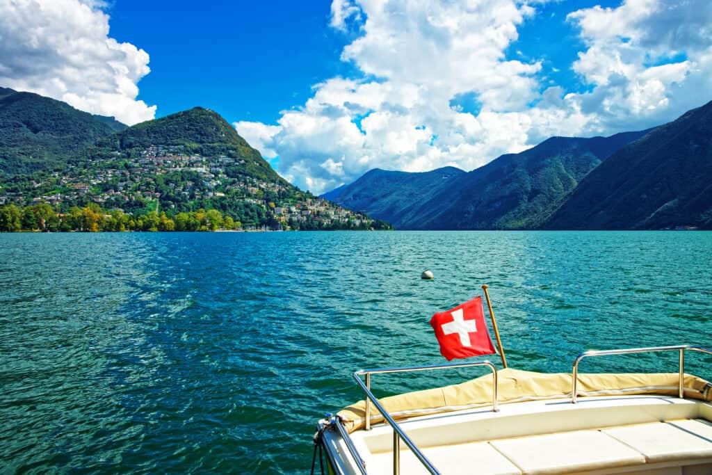 Boot met Zwitserse vlag op het meer van Lugano