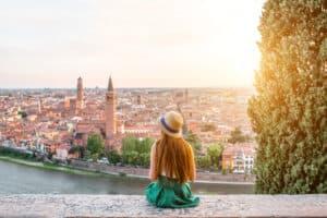 Jonge vrouw kijkt uit over de stad Verona in Italië