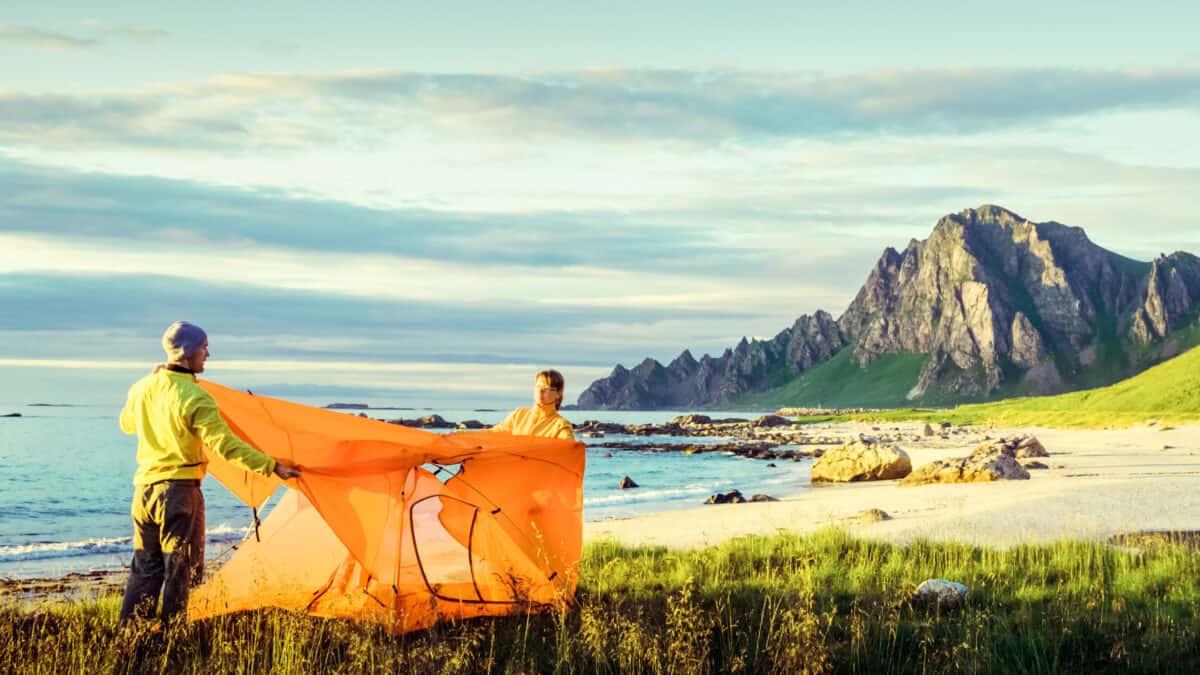 Man en vrouw zetten een tent op aan het strand en uitzicht op de bergen in Noorwegen