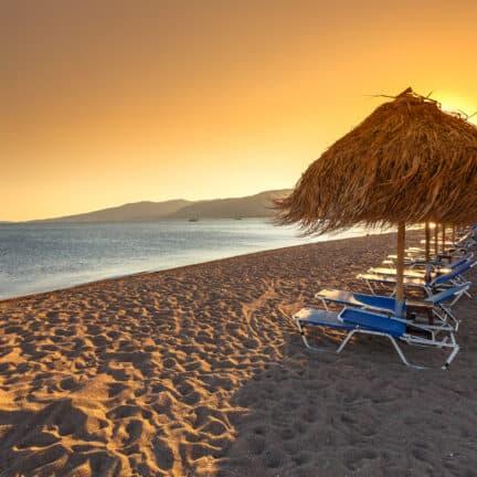 Parasols en ligbedden op een strand op Lesbos, Griekenland
