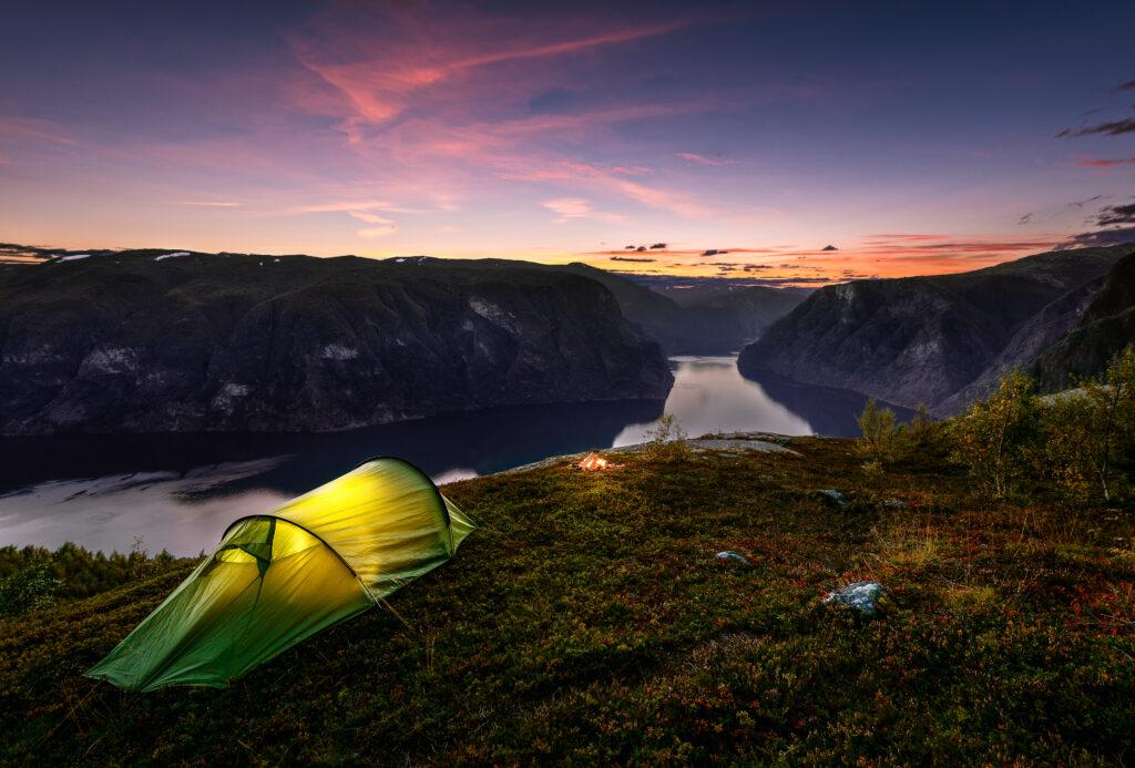Verlichte tent in de avond met uitzicht op de Aurlandsfjord in Noorwegen