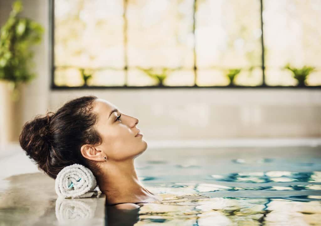 Vrouw ligt ontspannen in een zwembad van een wellness center