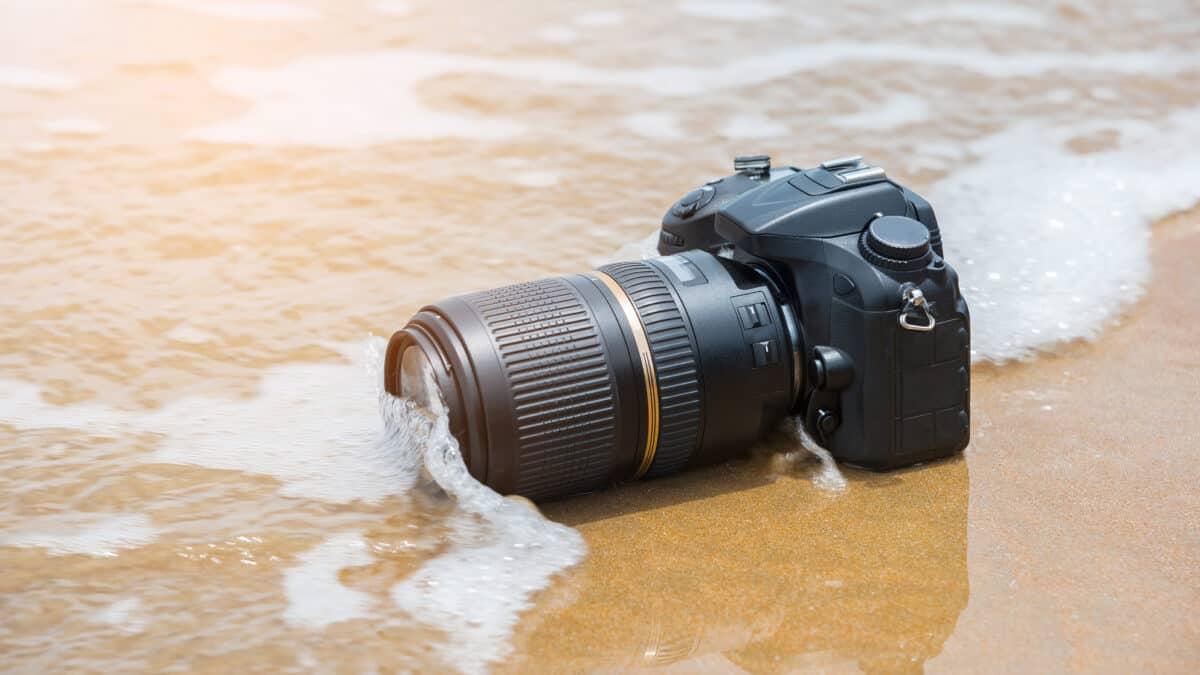 Spiegelreflexcamera wordt overspoeld door een kleine golf op het strand