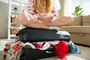 Jonge vrouw met bloemetjesjurk zit op een koffer die niet meer dicht wil door teveel kleding en schoenen