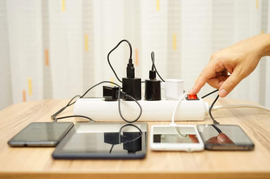Man drukt een stekkerdoos aan met veel aangesloten elektronica