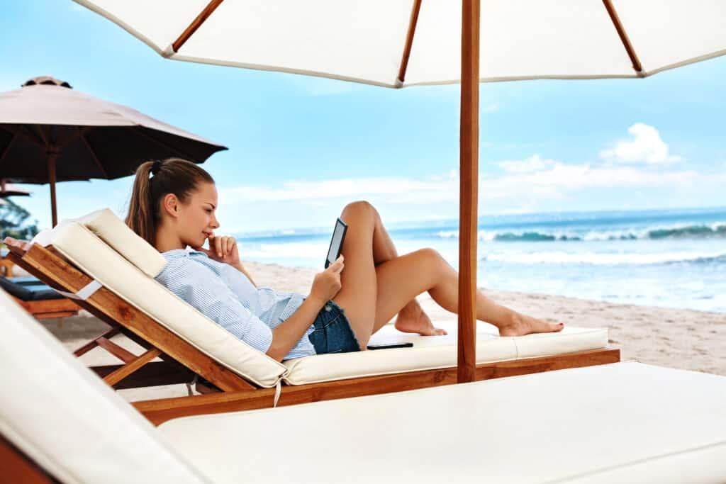 Vrouw met paardenstaart onder witte parasol leest een boek op een e-reader aan het strand