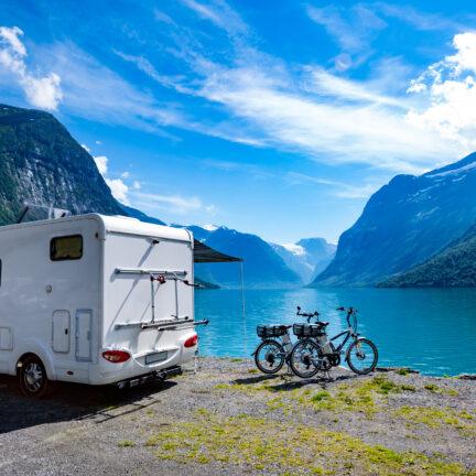 Witte camper met fietsen aan een meer en bergen in de verte