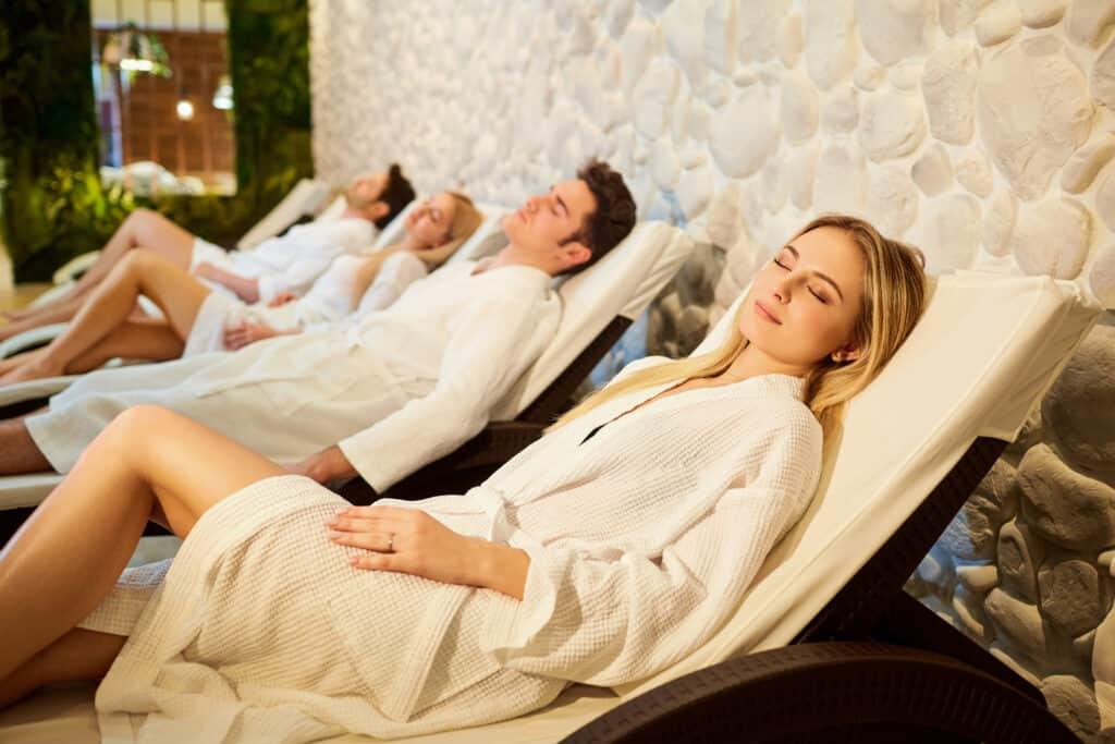 Mensen in badjassen rusten in de relaxruimte van de wellness
