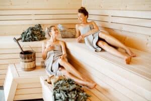 Twee vriendinnen in badhanddoek zitten te ontspannen in de sauna