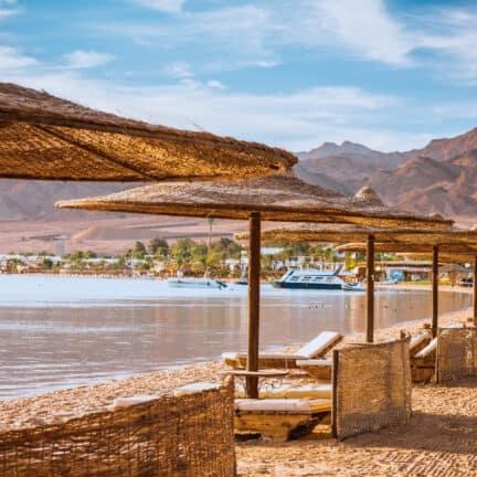 Rieten parasols en ligbedden op het strand bij de Rode Zee in Egypte
