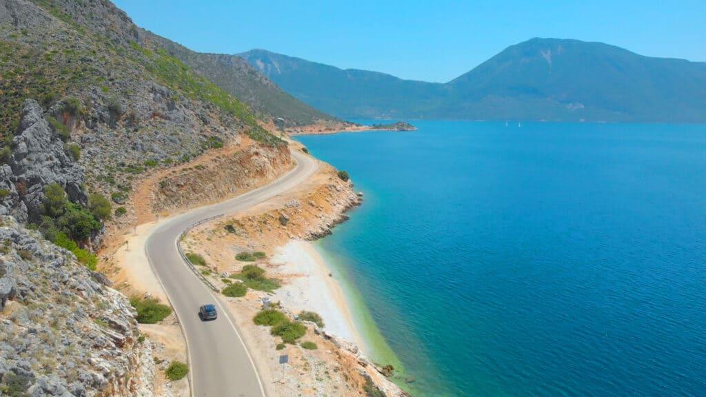 Auto rijdt langs de zee en kust van een eiland