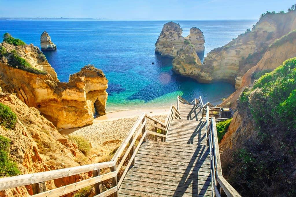 Houten brug naar het strand van Praia do Camilo