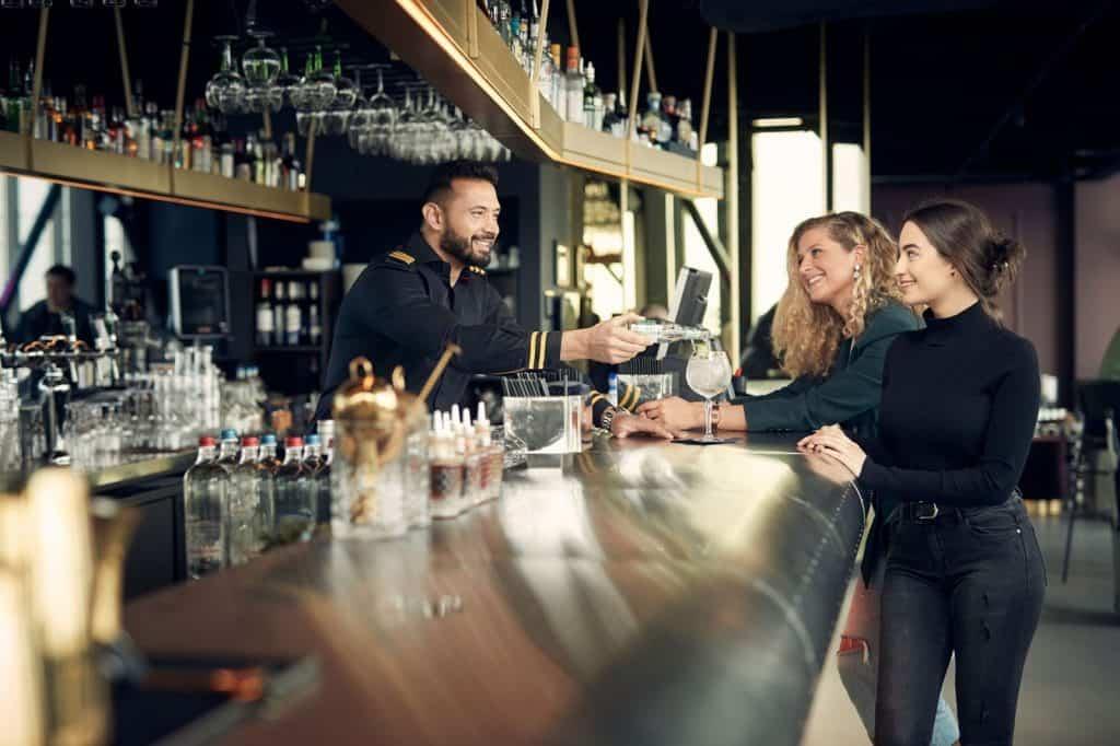 Twee vrouwen krijgen drankjes bij de bar