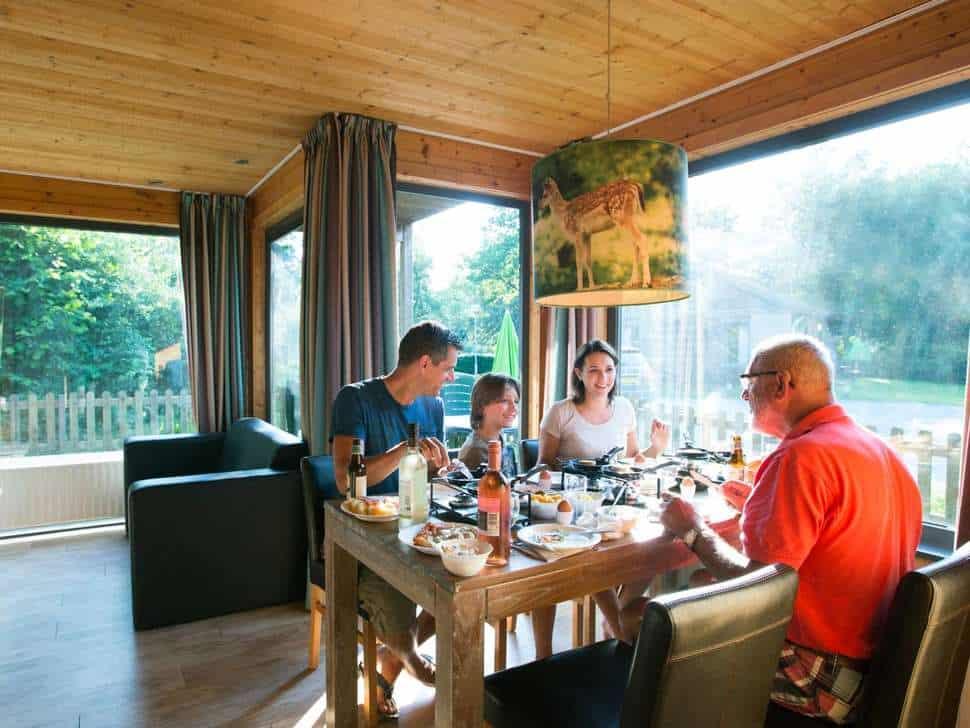Familie is gezellig samen aan het eten in een huisje van Vakantiepark Dierenbos