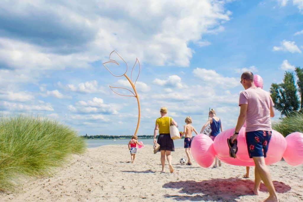 Familie wandelt naar het Veluwemeer met opblaasspullen