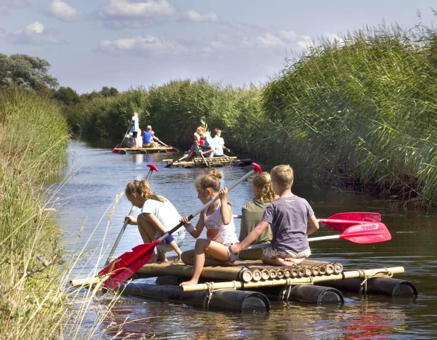 Kinderen aan het varen met een zelfgemaakt vlot