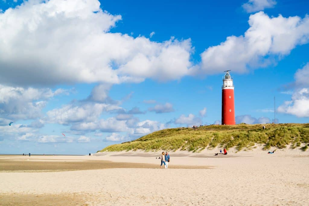 Mensen op het strand en de vuurtoren van Texel