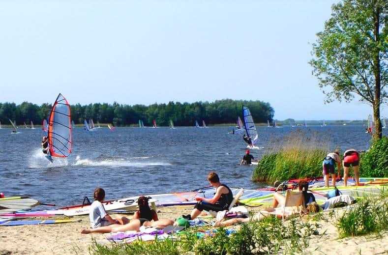 Mensen op het strand en windsurfers op het Veluwemeer