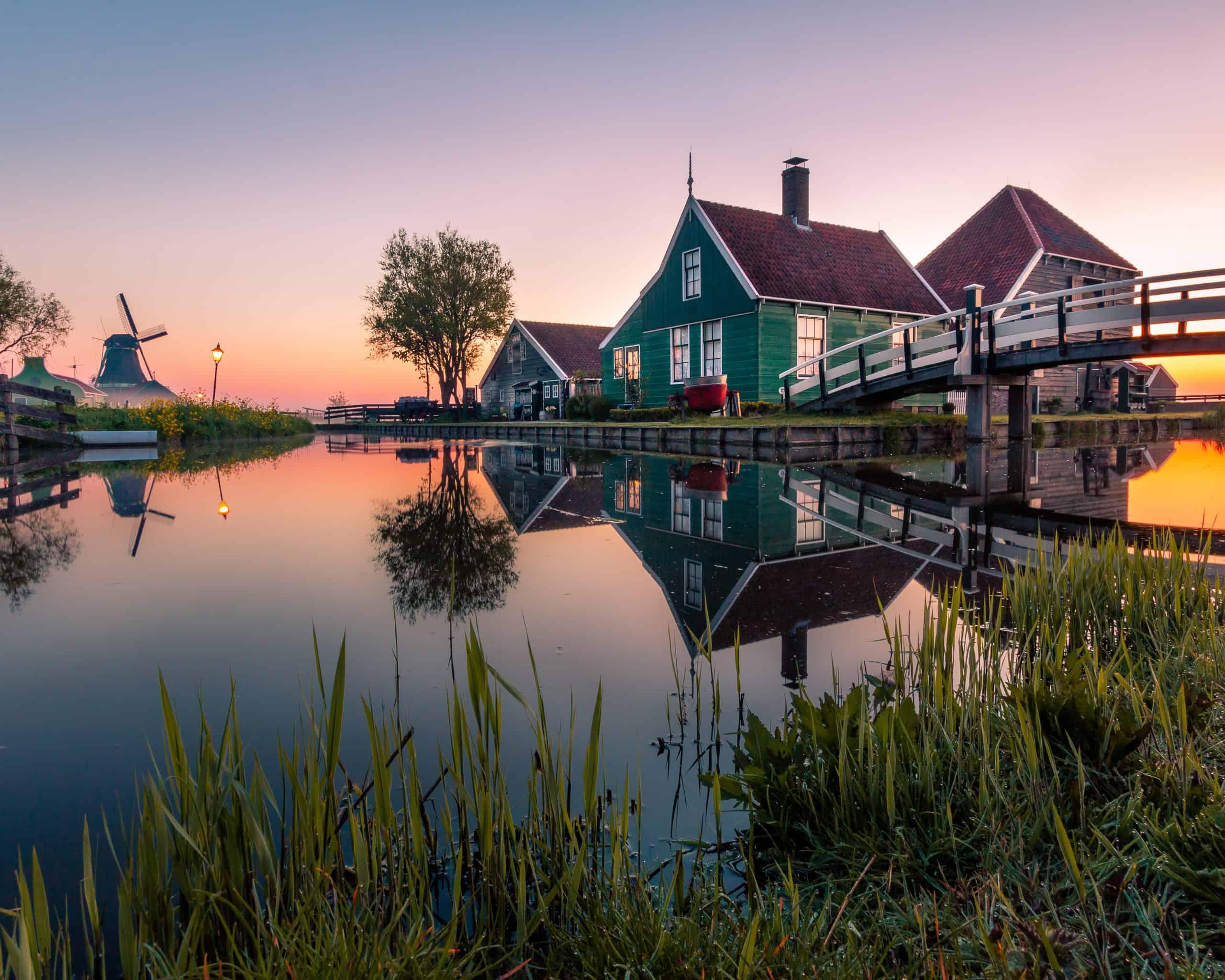 Huis bij een kanaal met een molen in Noord-Holland