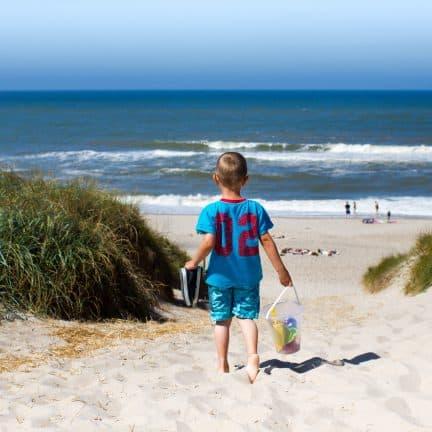 Kleine jongen loopt met strandspullen door de duinen richting het strand