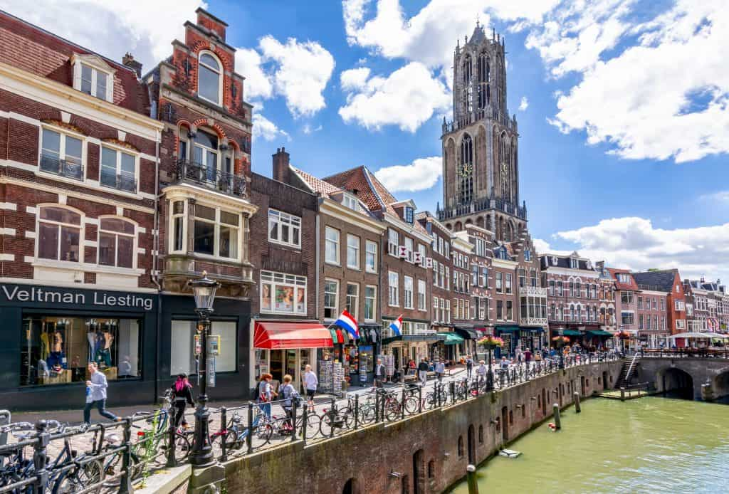 Winkelstraat langs de grachten en uitzicht op de Domtoren in Utrecht